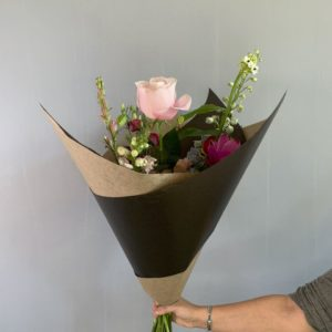 Foto van een ingepakt roze boeket met bloemen